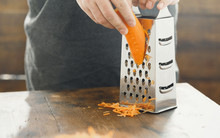 Close Up Male Hands Rubs Carrots On Grater