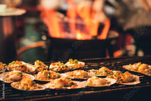 Grilled scallops sold at a street market stall with a pan covered with flames on the background Poster