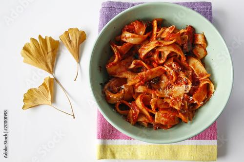 pasta tagliatelle with tomato sauce in a bowl on table cloth Fototapeta