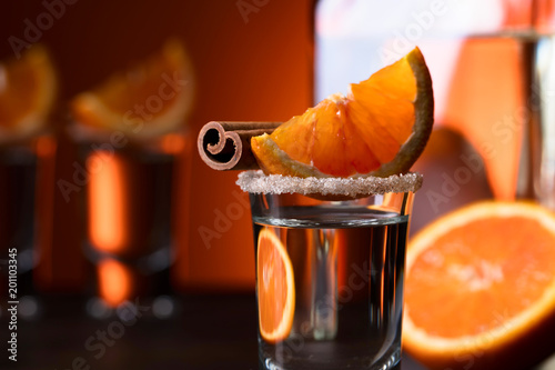 Foto op Plexiglas Oost Europa Glasses of tequila with orange and cinnamon sticks on a wooden table.