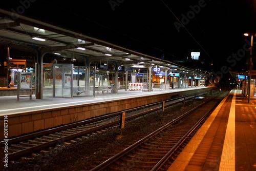 In de dag Treinstation Bahnsteig mit Nachtbeleuchtung / Der Bahnsteig des Bahnhofes Weinheim in der Nacht mit Sitzplätzen, Schienen und Glasunterständen.
