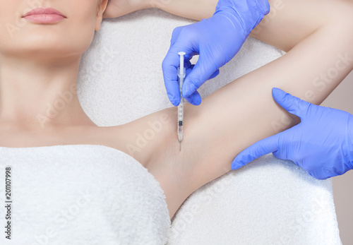 The doctor makes intramuscular injections of botulinum toxin in the underarm area against hyperhidrosis Canvas Print
