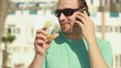 Happy man talking on cellphone and drinking, steadicam shot HD