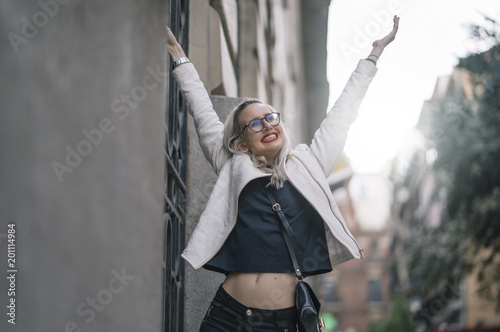 Young girl with glasses and white hair has fun streets of Madrid Spain.