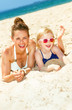 smiling modern mother and daughter in swimsuit on seashore