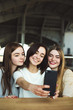 Three young women have fun and take selfie together