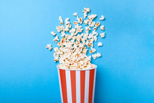 Spilled Popcorn And Paper Bucket In Red Strip On Blue Background. Copy Space For Text