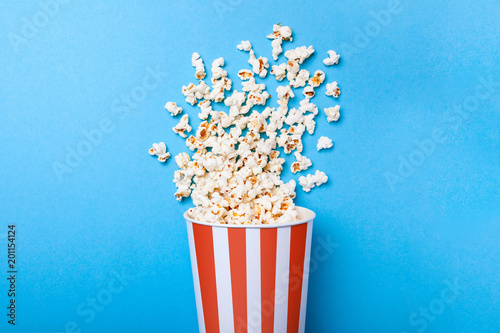 Fotografía  Spilled popcorn and paper bucket in red strip on blue background