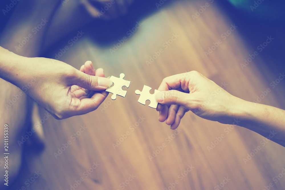 Fototapeta two hands trying to connect couple puzzle piece  Jigsaw alone wooden puzzle Teamwork, partnership, business idea, cooperation management concept