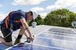 Solar panel technician with drill installing solar panels