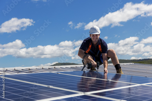 Solar panel technician with drill installing solar panels Fototapet