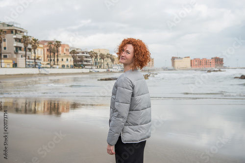 happy young woman in puffer jacket on seashore, Anzio, Italy Wallpaper Mural