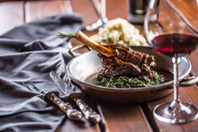 Roasted Or Confit Lamb Leg In Pan With Spinach And Red Wine