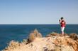 Tourist taking photos with phone at Ponta da Piedade, Lagos, Algarve, Portugal