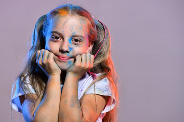 Kid with ponytails holds cheeks. Schoolgirl has paint spots