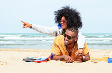 Young Afro American Couple  Pointing Finger Relaxing On Beach - Cheerful African Friends Having Fun At Day On Blue Ocean Background - Concept Of Lovers Happy Moments On Summer Holiday