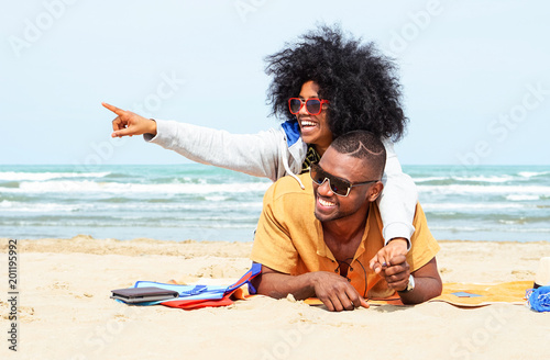 Fotografie, Obraz  Young afro american couple  pointing finger relaxing on beach - Cheerful african