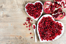 Pomegranate Seeds In A Shape Of A Heart On Wooden Background.