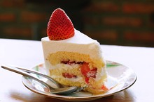 Close Up A Strawberry Shortcake Topped With A Large Fresh Strawberry Placed In White Plate And On Wooden Table With Cafe Environment.Victorian Sponge Cake With Cream And Strawberries.