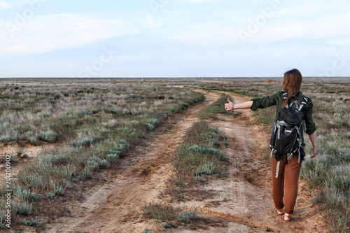 Fotografía  Girl hitchhiker on a country dirt road in steppe in the evening
