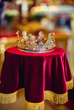 Gold Precious Crown For Wedding On Red Tablecloth. Closeup.