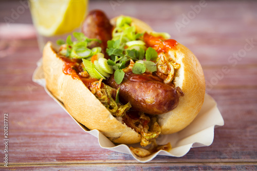 Asian hot dog, fried sausage, spicy chinese cabbage, hot chili sauce, spring onions, cress, bun