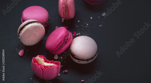 Macaroons on dark background, colorful french cookies macarons.Sweet dessert macaroon. The broken macarons with crumbs