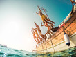 canvas print picture Group of happy friends diving from sailing boat into the sea - Young people jumping inside ocean in summer vacation - Travel and fun concept - Fisheye lens distortion