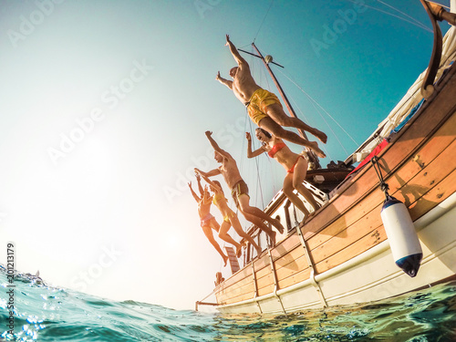 Fotografia  Group of happy friends diving from sailing boat into the sea - Young people jump
