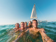 canvas print picture - Happy friends taking a selfie with action camera inside the ocean with sail boat in background