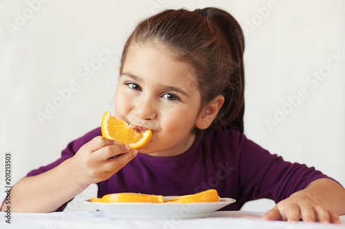 Photo little cute child girl dressed in a purple blouse holding an orange and eating o