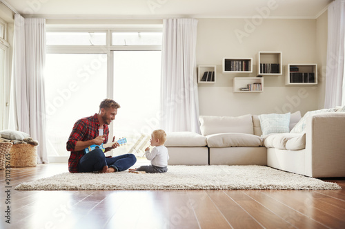 Photo  Father playing ukulele with young son in their sitting room