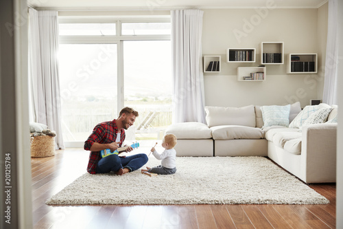 Valokuva  Father playing ukulele with young son in their sitting room