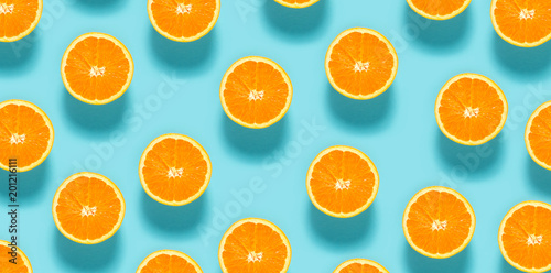 Tuinposter Vruchten Fresh orange halves on a blue background