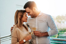 Image Of A Lovely Couple Drinking White Wine While Hugging.