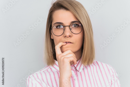 Fototapeta Closeup shot of serious attractive young European woman wearing pink shirt and round glasses keeping finger on her lips, having thoughtful indecisive look, thinking about something important. People obraz na płótnie