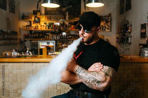 Brutal bearded man in sunglasses smoke an electronic cigarette and releases clouds of vapor at the vape shop Fototapet
