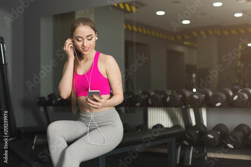Fitness girl in headphones choose music on phone Canvas Print