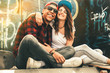 canvas print picture Young teen couple sitting by the wall and hangout at the street .Embrace each other and laughing .