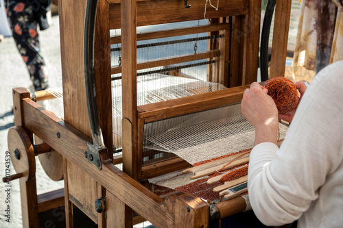 Fotografija Close up hands of woman weaving color pattern on traditional hand-weaving wooden