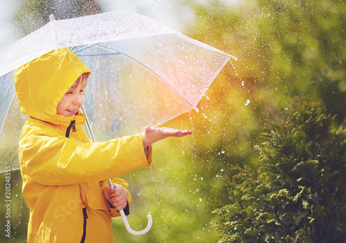 Fotografia happy kid catching rain drops in spring park