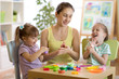 Woman and kids with play clay toys at day care center