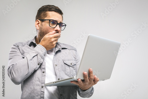 Fotografía  Wtf?! Omg! Oh no! Young amazed emotional brunet with bristle with sad grimace looks at screen of device, he can`t believe the bad news he received, gesturing with palms of arms