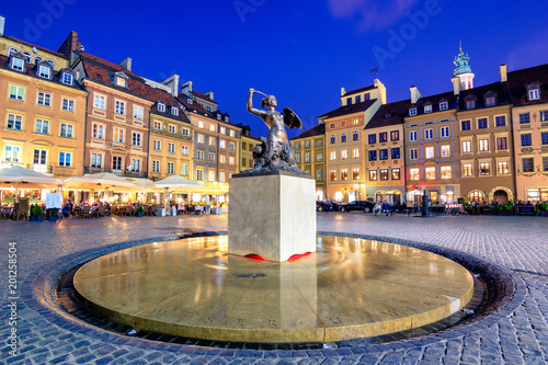 Fototapeta Night view of the bronze statue of Mermaid on the Old Town Market Square of Warsaw, surrounded by colorful old houses, Poland. obraz