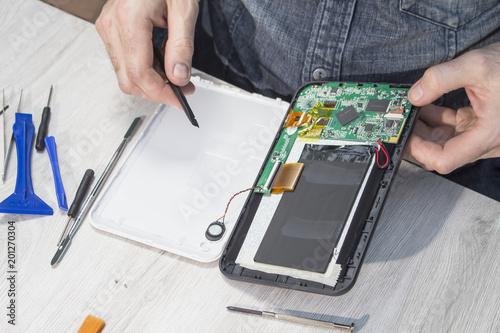Obraz Naprawa tabletu w serwisie. Rozkręcanie tabletu przez pracownika. - fototapety do salonu