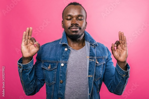 Valokuva  African gesticulates with his fingers okay standing with his eyes closed on a pi