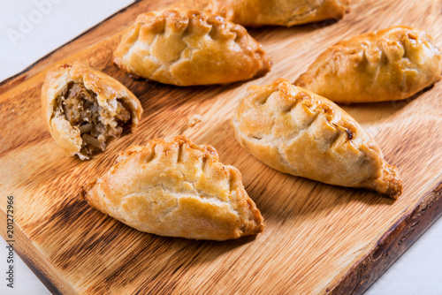 Hot pasties from butter enriched puff pastry filled with minced beef, potato, on Canvas-taulu