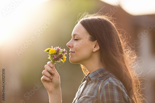 Obraz Pretty woman smelling flowers - fototapety do salonu