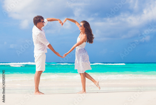 young happy couple in white making heart shape on tropical beach Obraz na płótnie