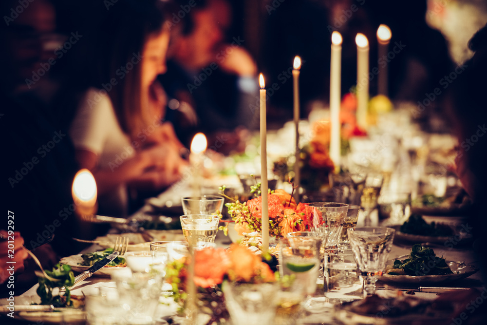 Fototapety, obrazy: People enjoy a family dinner with candles. Big table served with food and beverages.